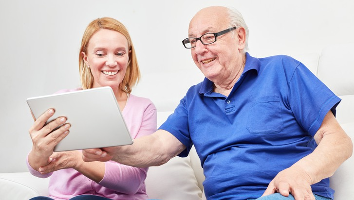 Young woman explains the social network and the video chat to a pensioner on the laptop