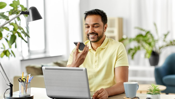 technology, communication and people concept - happy smiling indian with smartphone and laptop computer using voice command recorder at home office